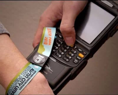 man holding rfid wristband onto rfid handheld reader to enter festival